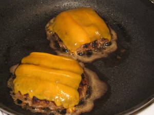 burgers in pan with melted cheese